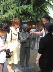 銅版路に建つ倪さんの像の説明を受ける笠井会長ら